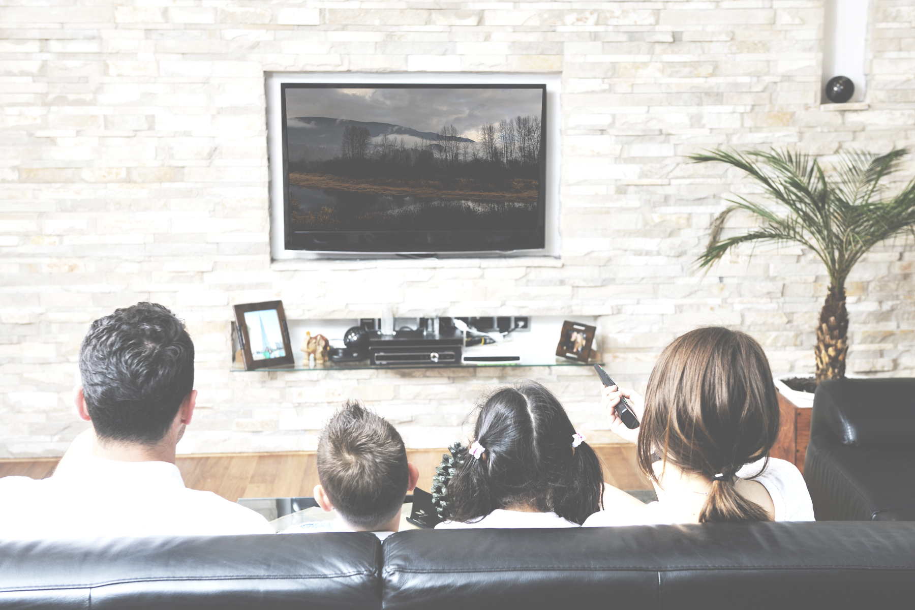 Family of four watching a movie on TV in their living room