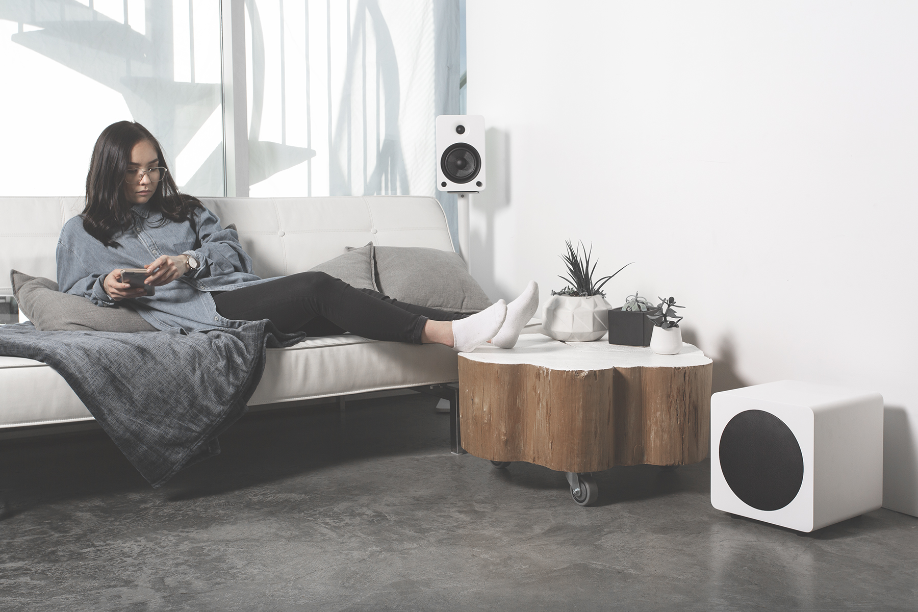 Woman listening to music while sitting on a couch with white YU4 and sub8 Kanto speakers
