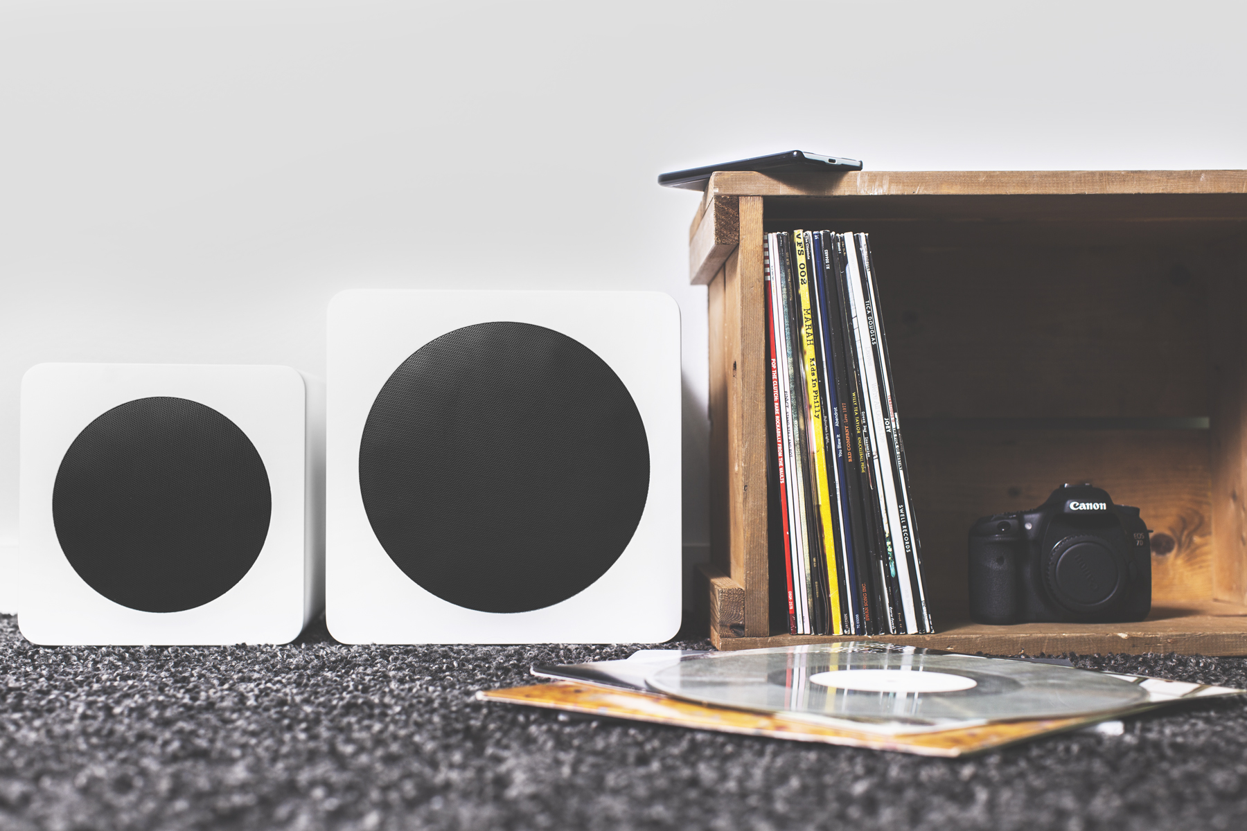 SUB6 and SUB8 subwoofers next to a record crate with records, a camera, and a cell phone